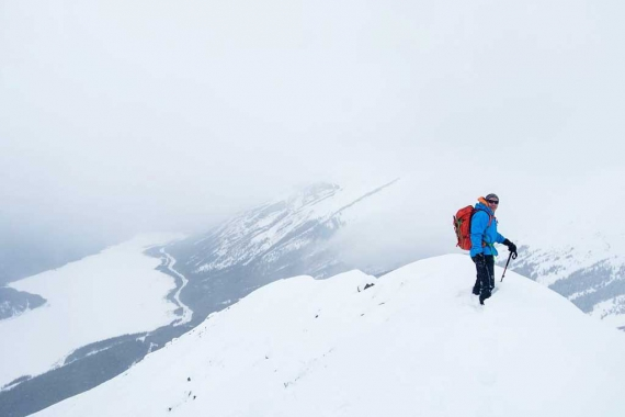 Winter backpacker on snowy mountain peak